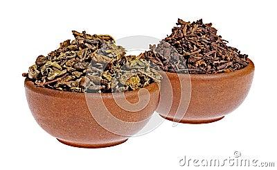 Té verde y negro seco en una taza de la arcilla
