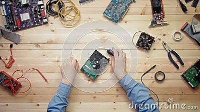 Técnico do computador da vista superior que repara o disco rígido na mesa de madeira com ferramentas e componentes eletrônicos filme