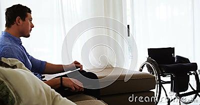 Télévision de observation d'homme handicapé sur le sofa 4k banque de vidéos