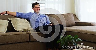 Télévision de observation d'homme handicapé sur le sofa 4k clips vidéos