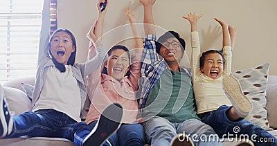 Télévision de observation de famille enthousiaste ensemble dans le salon 4k banque de vidéos