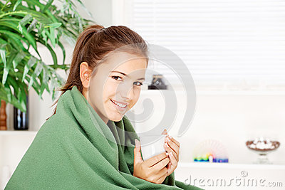 Té de consumición de la mujer en el país cubierto con la manta