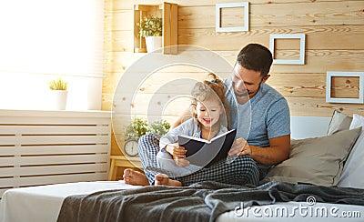 imagine stock despre  fericit familia tatăl şi fiica lectură carte pat