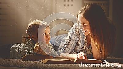 imagine stock despre  fericit familia mama şi fiica citit carte seara