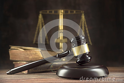 stock image of  judge gavel, old books and scales on a wooden table, justice symbols for balance and power in law and court, dark background with