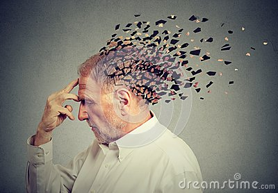 stock image of  memory loss due to dementia. senior man losing parts of head as sign of decreased mind function.