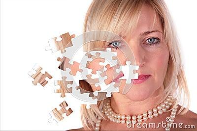 Ta av pussel från framsida av den middleaged kvinnan