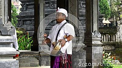 TABANAN, INDONESIA-GIUGNO, 16 2017: Un giocatore di gong al tempio di ulun danu beratan archivi video