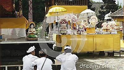 TABANAN, INDONESIA- JUNI, 16.2017: tre devoterade sitter och utövar sin religion på ulun danu bratan temple, bali arkivfilmer