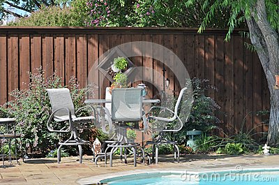 Outdoor patio table poolside under willow tree