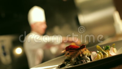 Table-Ready Meat against Chef Cooking Flambe. Table-ready meat dish is standing on the counter in the foreground. In the background chef is cooking flambe meat