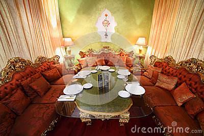 Table with serving and sofas in eastern restaurant