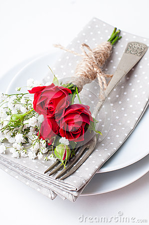 Festive table setting with red roses, napkins and vintage crockery on ...