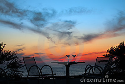 Table with two glasses of wine on sunset on sea