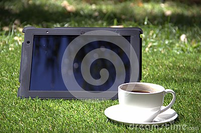 Tablet pc and a cup of coffee on the grass