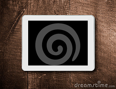 Tablet touch computer on a background of wood.