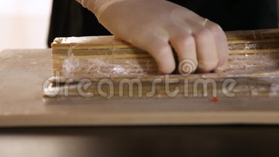 Taglio di mani di chef che arrotola un sushi di tappeto di bambù Processo di fabbricazione del sushi Riso, nori, avocado, granchi stock footage