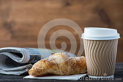 Take away coffee and fresh croissant and newspaper Stock Photo