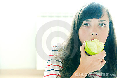Taking a bite of a green apple