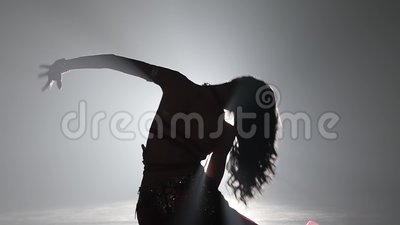 Talanted exotic belly dancer girl go on dance . Smoke background. Close up. Sihouette. Talanted long haired exotic belly dancer girl go on dance . Smoke stock footage