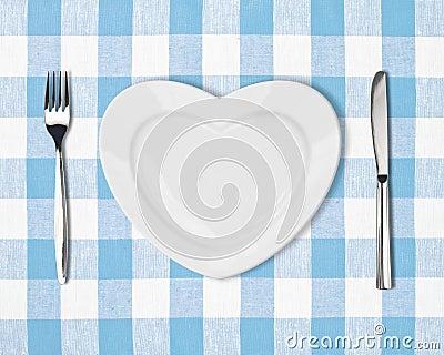 Talerz w kształcie serce, stołowy nóż i rozwidlenie na błękitnym tablecloth,