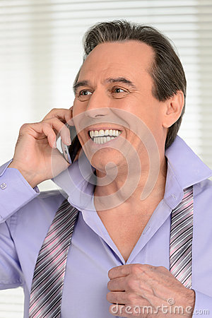 Talking to his loved ones. Cheerful mature businessman dressing