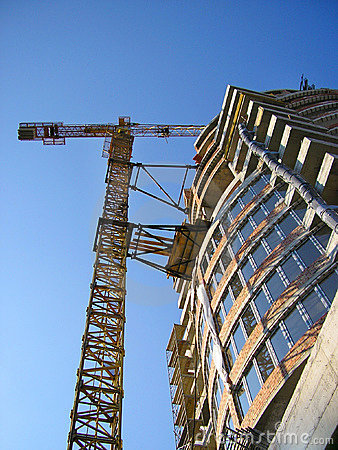 Tall orange crane constructing a new business building