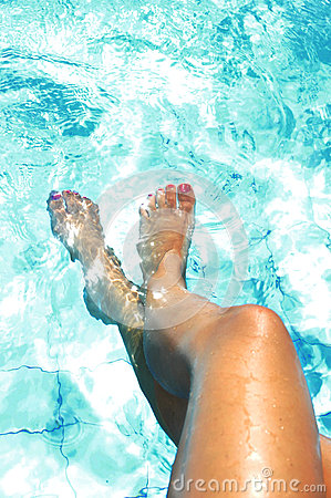 Tan Golden Legs Of Young Woman And Feet Painted Nails Having Suntan At Swimming Pool Stock Photo