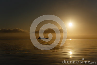 Tanker ship silhouetted on horizon at sunrise San Francisco Bay