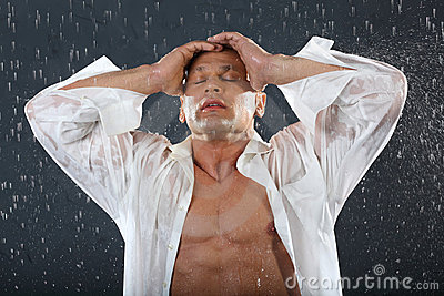 Tanned bodybuilder stands in rain