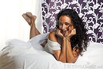 Tanned girl on bed - head in hands