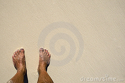Tanned legs on sand beach