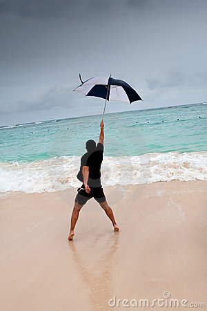 Tanned man jump with umbrella in blue sea