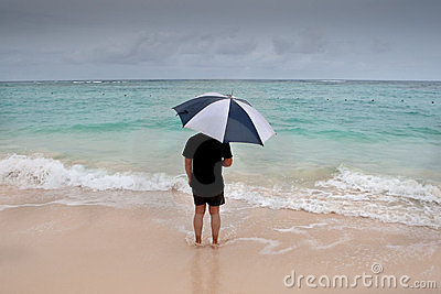Tanned man stand with umbrella in blue sea