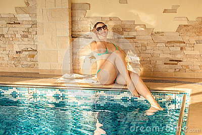 Tanned woman lying at pool on sunny day