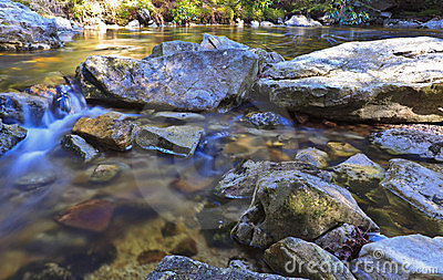 Tannin colored mountain stream and rocks