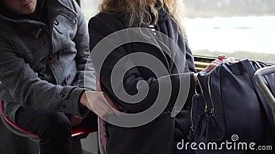 Taschendieb, der Telefon von einer Frau ` s Tasche in der Tram oder im Bus stiehlt stock video footage