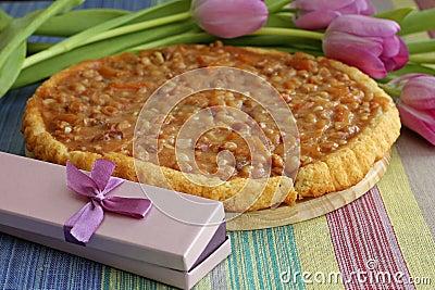 Tasty caramel tart with purple gift box
