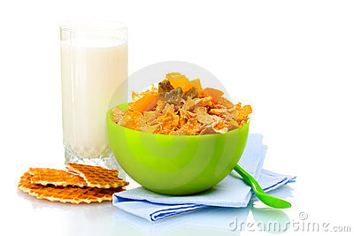 Tasty cornflakes in green bowl and glass of milk