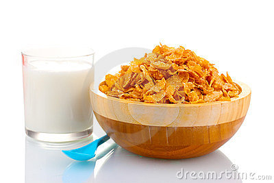Tasty cornflakes in wooden bowl and glass of milk