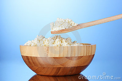 Tasty cottage cheese in bowl and spoon