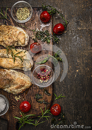 Tasty roasted chicken fillet with herbs,spices,seasoning and tomatoes on vintage gutting board over rustic wooden background, top Stock Photo