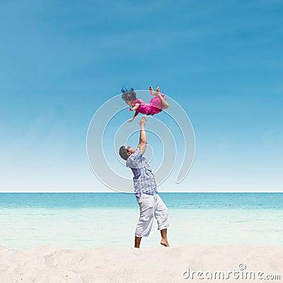 Tata miotania córka w powietrzu przy plażą