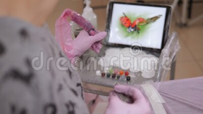 Tattoo master taucht eine Tätowiermaschine mit nadeln in tinte, vorbereiten ein tätowieren stock video