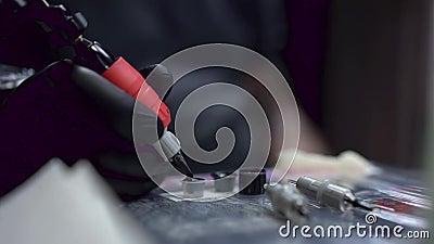 Tattooist S Hand In A Black Glove Dunks A Tattoo Gun Into Tattoo Ink