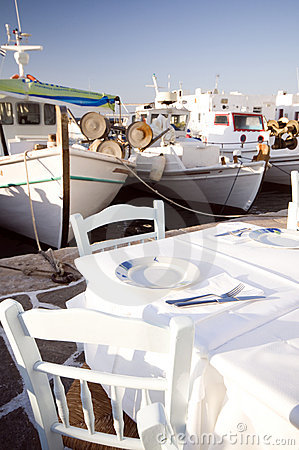 Taverna setting in harbor with fishing boats