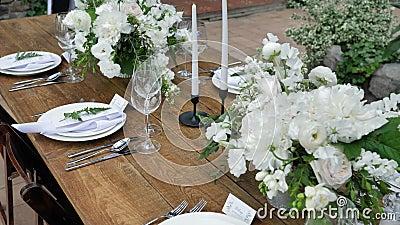 Tavoli decorativi con mazzi di fiori freschi con candele e decorazioni per un matrimonio o una festa per una festa di famiglia archivi video