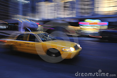Taxi cab speeding down street in a blur