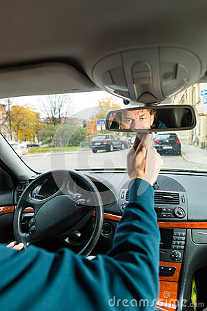 Taxi driver is looking in the driving mirror