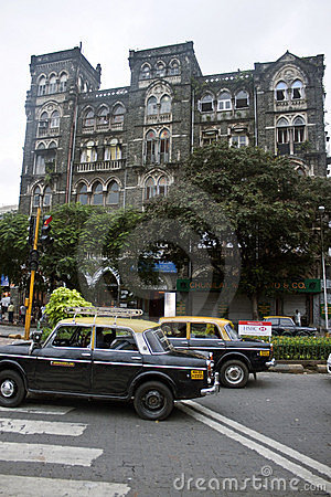 Taxis drive on a street in Mumbai Editorial Stock Image